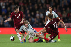 England's Tom Davies is tackled by Latvia's Roberts Uldriks and Raivis Andris Jurkovskis during the 2019 UEFA Euro U21 Qualifying, Group 4 match at the Vitality Stadium, Bournemouth.