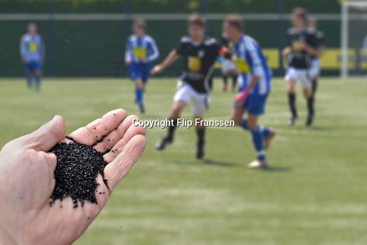 Nederland, Nijmegen, 8-10-2016 Een voetbalveld van kunstgras . De zwarte korrels van gemalen, rubberen autobanden, zijn in opspraak gekomen omdat ze kankerverwekkend zouden zijn. (Foto is een montage)Foto: Flip Franssen