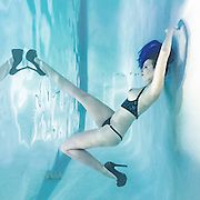 Dark Haired woman with blue topless blue bikini in high heels, breaks the surface from underwater<br /> <br /> Underwater Beauty by Craig Minielly