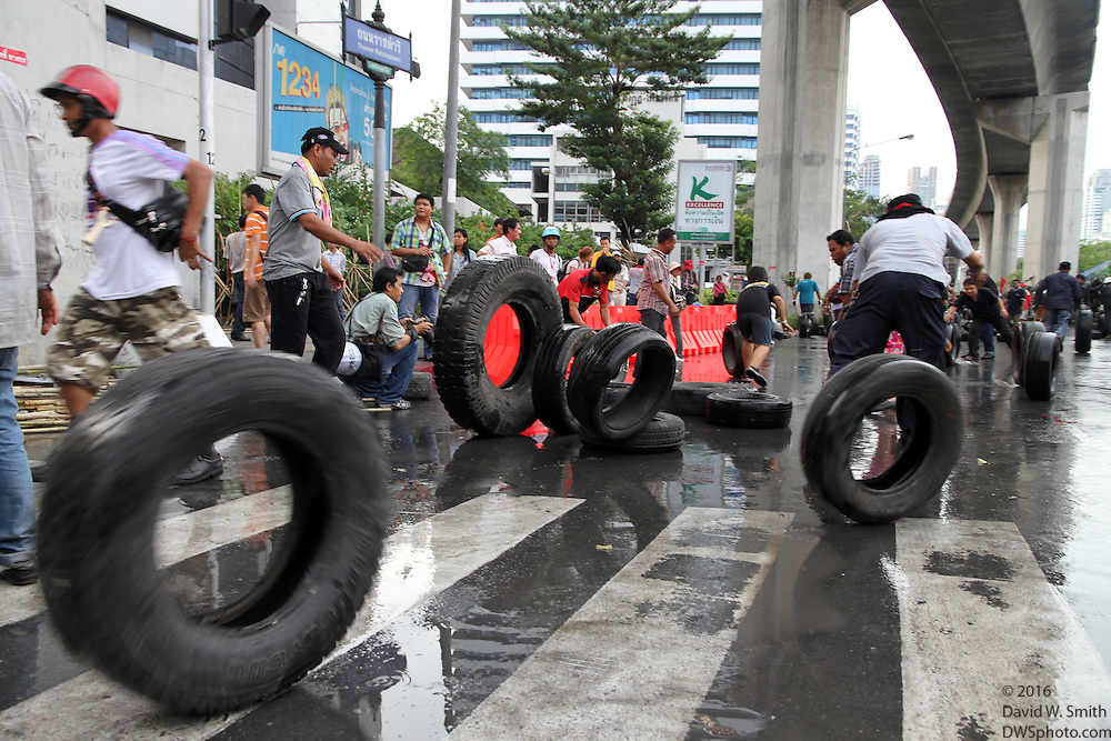 Protestors roll tires while dismantling a barricade during the Red Shirts anti-government protest in the Silom area of Bangkok.