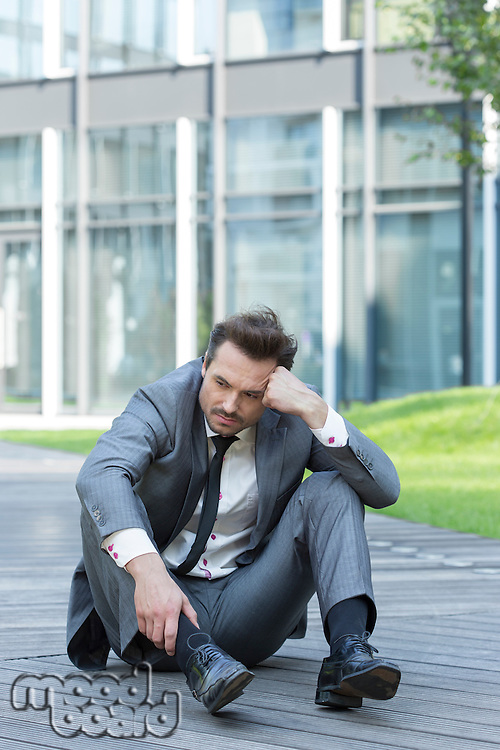 Full length of stressed businessman sitting on path outside office