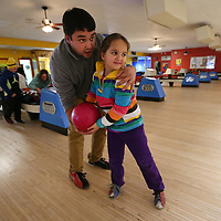 Artyom Butsykin, of Winfield Alabama, helps his daughter, Meri, 6, line up the for her best shot for a strike as they bowl at Rebel Lanes with friends and family on Wednesday afternooon in Tupelo. Artyom, and his family, came to Tupelo with friends from Winfield to get out of the house and to have a break from the winter weather.