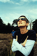 Cold man in sunglasses starring at eclipse, sea side, UK 1999.