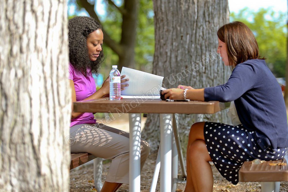 Chelsea S. Belote, Assistant Director, Office of Student Success, (in blue) meets with Christina Jenkins, Success Coach in the Office of Student Success outside Ronan Hall (purple). Photo by Steve Jessmore/Central Michigan University