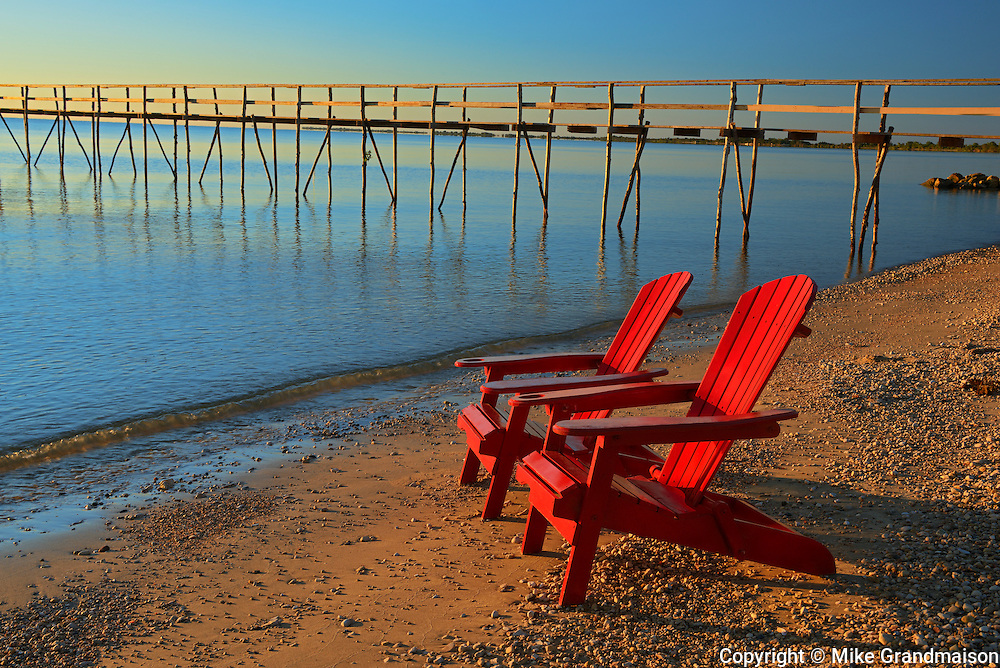 Muskoka chairs and pier on Lake Winnipeg<br />