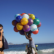 A ball seller walks along Ipanema beach carrying his collection of beach balls. Rio de Janeiro,  Brazil. 4th July 2010. Photo Tim Clayton..The beaches of Rio de Janeiro, provide the ultimate playground for locals and tourists alike. Beach activity is in abundance as beach volley ball, football and a hybrid of the two, foot volley, are played day and night along the length and breadth of Rio's beaches. .Volleyball nets and football posts stretch along the cities coastline and are a hive of activity particularly at it's most famous beaches Copacabana and Ipanema. .The warm waters of the Atlantic Ocean provide the ideal conditions for a variety of water sports. Walkways along the edge of the beaches along with exercise stations and cycleways encourage sporting activity, even an outdoor gym is available at the Parque Do Arpoador overlooking the ocean. .On Sunday's the main roads along the beaches of Copacabana, Leblon and Ipanema are closed to traffic bringing out thousands of people of all ages to walk, run, jog, ride, skateboard and cycle more than 10 km of beachside roadway. .This sports mad city is about to become a worldwide sporting focus as they play host to the world's biggest sporting events with Brazil hosting the next Fifa World Cup in 2014 and Rio de Janeiro hosting the Olympic Games in 2016...