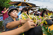 "12 JULY 2014 - PHRA PHUTTHABAT, SARABURI, THAILAND: People put flowers on the temple's car during the Tak Bat Dok Mai at Wat Phra Phutthabat in Saraburi province of Thailand. Wat Phra Phutthabat is famous for the way it marks the beginning of Vassa, the three-month annual retreat observed by Theravada monks and nuns. The temple is highly revered in Thailand because it houses a footstep of the Buddha. On the first day of Vassa (or Buddhist Lent) people come to the temple to ""make merit"" and present the monks there with dancing lady ginger flowers, which only bloom in the weeks leading up Vassa. They also present monks with candles and wash their feet. During Vassa, monks and nuns remain inside monasteries and temple grounds, devoting their time to intensive meditation and study. Laypeople support the monks by bringing food, candles and other offerings to temples. Laypeople also often observe Vassa by giving up something, such as smoking or eating meat. For this reason, westerners sometimes call Vassa ""Buddhist Lent.""    PHOTO BY JACK KURTZ"