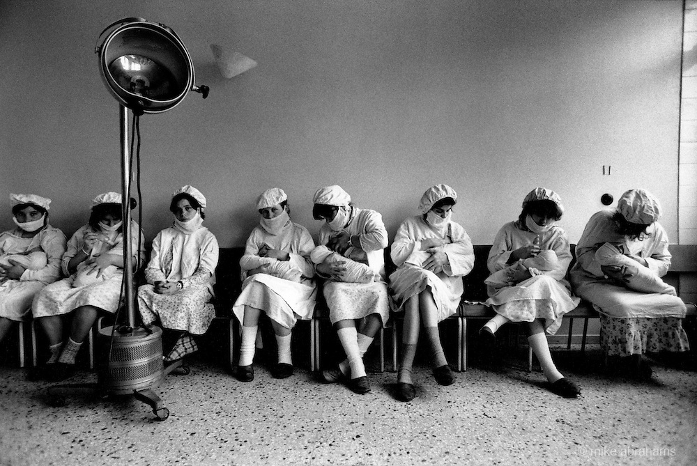 Women lined up against the wall feed their newborn babies. Maternity Unit at Bucharest Hospital. Romania Feb 1990