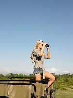 Young woman on safari standing in jeep looking through binoculars side view
