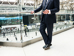 Businessman Using Cell Phone at Railway Terminal