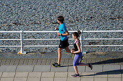 © London news pictures. 25/03/2017. Aberystwyth, UK.<br /> Two poeople out jogging on a day of glorious sunshine and clear blue skies in Aberystwyth on the west wales coast, with temperatures expected to reach 18 or 19∫c by the afternoon.  Sheltered from the cooling effects of an easterly wind, West Wales is expected to be the warmest pace in the UK today (Sat). Photo credit: Keith Morris/LNP