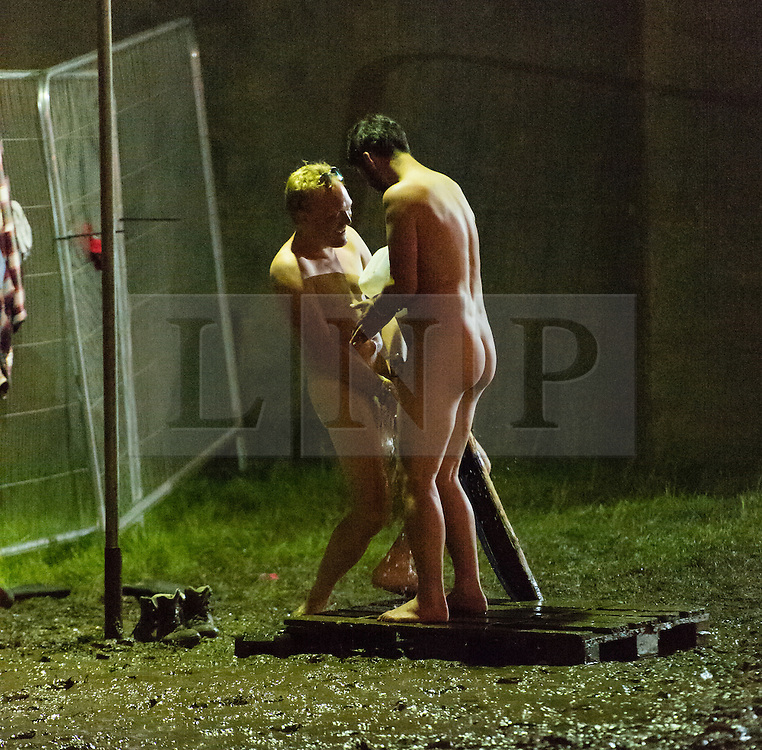 © Licensed to London News Pictures. 27/06/2015. Glastonbury Festival, UK.  Two naked male Glastonbury Festivalgoers watching themselves under a tap openly in the campsite on Saturday Day 4 of the festival, in the early hours of Sunday morning while other festival goers walk past watching and laughing.    It is Glastonbury Festival 2015.  This years headline acts include Kanye West, The Who and Florence and the Machine, the latter being upgraded in the bill to replace original headline act Foo Fighters. Photo credit: Richard Isaac/LNP