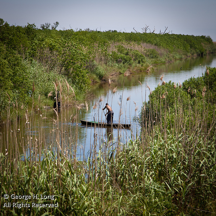 shirtless black man in pirogue fishing for crawfish in Plaquemines Parish