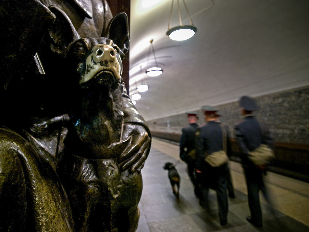 "Police with dog at the Moscow subway station ""Ploshchad Revoluyutsii"" (Revolution Square) which is devoted to glorify the the lives, work and heroism of the ordinary men and women of the Russian Revolution. People are touching a dogs nose for a moment to be lucky and to fulfil a future wish."