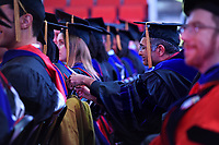 A graduate student assists a fellow grad with fixing her gown at the 2017 Winter Commencement at PNC Arena.