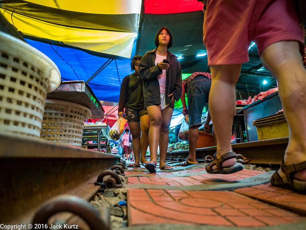 27 SEPTEMBER 2016 - BANGKOK, THAILAND: People walk along the railroad right of way in the market in the Samut Songkhram train station. The train from Baen Laem to Samut Songkhram (Mae Khlong) recently resumed service. The 33 kilometer track was closed for repair for almost a year. In Samut Songkhram, the train passes over the market. Vendors pull their stands out of the way and people step out of the way as the train passes through the market. It is one of the most famous train stations in Thailand and has become an important tourist attraction in the community.     PHOTO BY JACK KURTZ