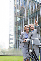 Happy businessman showing something to businesswoman in city