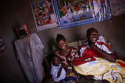 Ngombe Naikatya, 33 years old sits within her home with her husband Denis, her newborn son Andre and 16 month old daughter Esperence in her village after a three hour walk from the hospital in Walungu, Bukavu, South Kivu, Democratic Republic of Congo on November 25, 2014. Ngombe Naikatya, 33 years old had her second caesarian procedure at the Walungu hospital. She has a 16 month old daughter Anastasia who is taken care of by her father and his parents back in their village. Ngombe has taught at primary school for the last 4 years after completing a diploma of education. CRS with the support of donors USAID and Glaxo Smith Kline is improving the health of newborn babies (0-28 days) and pregnant women in the province of South Kivu. The Afya Mama na Mtoto (Healthy Babies and Mothers) 3 year project is being implemented by CRS in collaboration with health structures within the two targeted health zones of Walungu and Nyangezi. The project supports community- based facilities to conduct health activities for increased access and quality of intra-partum and post-partum care.
