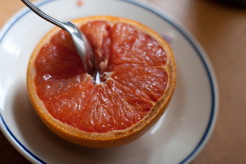 Spoon in a grapefruit half on a plate.