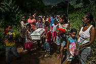 "URDANETA, VENEZUELA - AUGUST 17, 2017: Children carried the coffin of three-month old, Kleiver Enrique Hernández for over two and a half hours, over hills and through shallow streams, during his funeral procession to the cemetery from the rural farming area where he lived with his family. Kleiver was born healthy, weighing 8 pounds 2 ounces - however his mom Kelly Hernández could not physically nurse him. Despite searching endlessly, Ms. Hernández and her boyfriend, César González, could not find or afford infant formula for their son. It was not for lack of trying. Online inventory searches of Locatel, one of the largest pharmacy chains in Venezuela, found that only one of its 64 locations across the country reported having the infant formula doctors had prescribed for Kleiver in stock. It is unlikely that Ms. Hernández could have afforded it anyway. Hyperinflation has shriveled wages paid in the local currency, bolívars, to a small fraction of what they were worth two years ago. A month's worth of the formula Kleiver needed cost more than twice the entire monthly salary that Mr. González earned as an agricultural worker. Formula shortages hit the hospitals too. Doctors in the emergency room at Dr. Domingo Luciani hospital said they had no formula in stock to feed patients like Kleiver. With so few options, Kleiver's mother warily prepared bottles of cornstarch and water, occasionally with whole milk, when they could find it. It was not enough. His parents had taken him to three different emergency rooms. Each hospital was full. ""I was desperate – and seeing so many, so many children in the same situation as our boy,"" said Ms. Hernández. When they were admitted to Dr. Domingo Luciani, they were tremendously relieved. But soon they watched a steady stream of parents arriving with malnourished babies, only to leave crying: ""My child has died!"" They waited anxiously for Klevier's condition to improve, sleeping in a chair by his side, or in the"