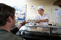 Sushi chef handing sushi to customer in restaurant