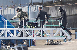 © Licensed to London News Pictures. 12/02/2018. London, UK. Members of the Royal Navy Bomb Disposal Team carry equipment ashore after diving at the location of the unexploded bomb next to London City Airport which remains closed. A World War II era bomb was found in The River Thames during routine work on nearby King V Dock. Police have evacuated nearby residents, closed the airport and set up a 214-metre exclusion zone. Photo credit: Peter Macdiarmid/LNP
