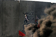 Palestinian youths throw rocks over a wall at Israeli troops, during a demon    stration at the concrete seperation barrier in the West Bank town of Qalqily    a, Saturday, Dec. 27, 2003. Hundreds of Palestinians protested against the c    onstruction of the barrier, which the Israeli Government says is necessary t    o prevent suicide bombings. Palestinians say it amounts to a seizure of land     where they hope to build an independent state.(Photo by Heidi Levine/Sipa P    ress).