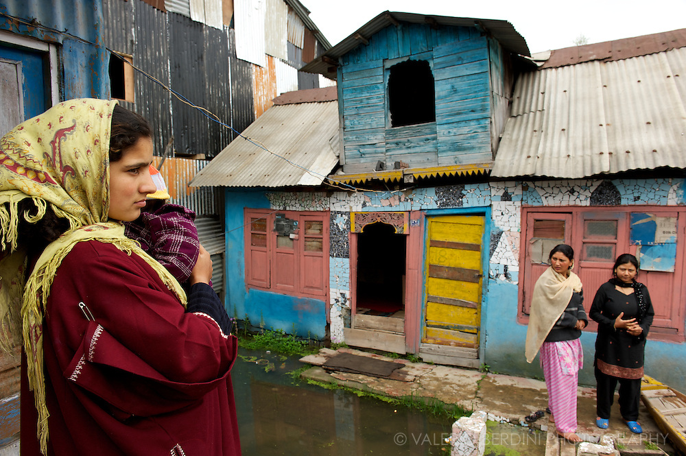 Young mother in her doorstep protects her baby in traditional Kashmiri dress. Dal Lake. Srinagar. Kashmir. India.