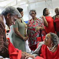 Pastor J.O. Barrentine greets Mary Minnis at her 100th birthday party, which featured choirs, speakers, scripture and prayer, reflections by several local pastors and dozens of her family and friends.