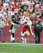 LANDOVER, MD - NOVEMBER 26:  Cornerback Richard Marshall #31 of the Carolina Panthers intercepts a pass intended for wide receiver Santana Moss #89 of the Washington Redskins at FedExField on November 26, 2006 in Landover, Maryland. The Redskins defeated the Panthers 17-13. ©Paul Anthony Spinelli *** Local Caption *** Richard Marshall;Santana Moss