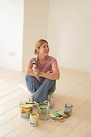 Smiling woman sitting with painting materials on floor