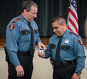 Jose Quirin, right, is presented his ID by Chief Mock, left, after receiving his badge during a swearing-in ceremony for new officers at the Houston ISD Police Department, March 3, 2014.