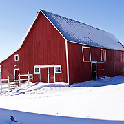 Landscape of red barn with white fence on snowy winter day