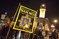 © Licensed to London News Pictures . 21/08/2012 . London , UK . Protesters march from Lambeth Town Hall ( in the background ) to Brixton police station to demonstrate against deaths in police custody . Relatives of Sean Rigg , who died in police custody in August 2008 , lead the march . Video has emerged of a man being detained in Brixton on Sunday ( 19th August ) during which it is alleged police officers stamped on his head . Protesters delivered a formal complaint about the incident to the counter of Brixton Police Station , following the march . Photo credit : Joel Goodman/LNP