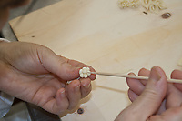 artisan making bread decoration using a shaped woodden stick for engraving small leaves of a flower shape dough.