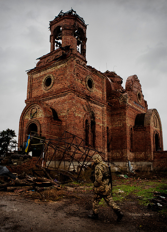 Pisky, Nr Avdiivka, eastern Ukraine, Nov. 2017.<br /> <br /> A serviceman of the Ukrainian army, walks past the bombed church in the devastated village of Pisky, on the outskirts of Avdiivka in eastern Ukraine.<br /> <br /> The village is on the front-line and under frequent attack by sniper, rocket and artillery fire from pro-Russian separatists.