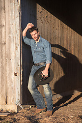 Good Looking cowboy by a rustic barn