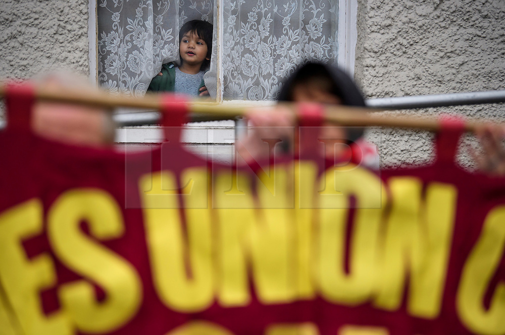 **NOTE TO EDITORS: An young girl is pictured in the image** © Licensed to London News Pictures. 07/01/2017. London, UK. A young muslim girl looks on out of a window as members of Kent Anti-Racism Network erect a banner outside Mote Road Islamic centre mosque in Maidstone, Kent as far-right group The South East Alliance protest against expansion of the mosque. Plans to redevelop Maidstone Mosque into a purpose-built centre with three shops have been approved by  Maidstone Borough Council. A counter demonstration is Organised by The Kent Anti-Racism Network. . Photo credit: Ben Cawthra/LNP