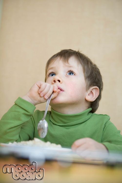 Portrait young boy gazing upwards with spoon in his hand