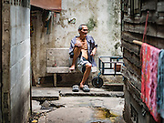 15 AUGUST 2016 - BANGKOK, THAILAND: A resident of the Pom Mahakan slum sits against the old Bangkok city wall Monday, before eviction notices were put up around the slum. Final eviction notices were posted today and residents of the slum have been told they must leave the fort by September 3, 2016. The Pom Mahakan community is known for fireworks, fighting cocks and bird cages. Mahakan Fort was built in 1783 during the reign of Siamese King Rama I. It was one of 14 fortresses designed to protect Bangkok from foreign invaders. Only two of the forts are still standing, the others have been torn down. A community developed in the fort when people started building houses and moving into it during the reign of King Rama V (1868-1910). The land was expropriated by Bangkok city government in 1992, but the people living in the fort refused to move. In 2004 courts ruled against the residents and said the city could take the land.      PHOTO BY JACK KURTZ