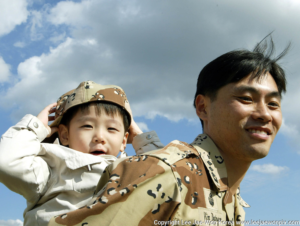 A South Korean captain from an unit of non-combat troops, carries his son on his back on the eve of his departure to Iraq at a departure ceremony at a military unit<br /> in Gwangju, about 40 km (25 miles) southeast of Seoul October 14, 2003. /Lee Jae-Won