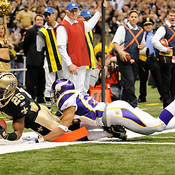 Jan 24, 2010; New Orleans, LA, USA; New Orleans Saints running back Reggie Bush (25) dives into the endzone past Minnesota Vikings cornerback Cedric Griffin (23) during the second half of the 2010 NFC Championship game at the Louisiana Superdome. Mandatory Credit: Derick E. Hingle-US PRESSWIRE