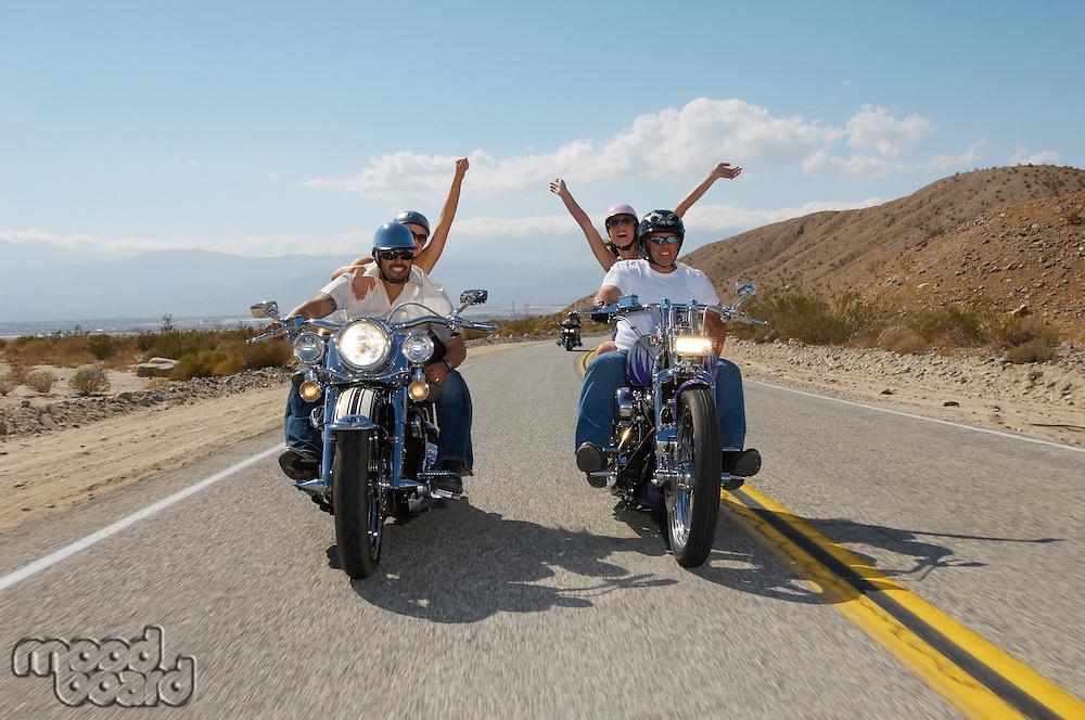 Bikers riding on desert road