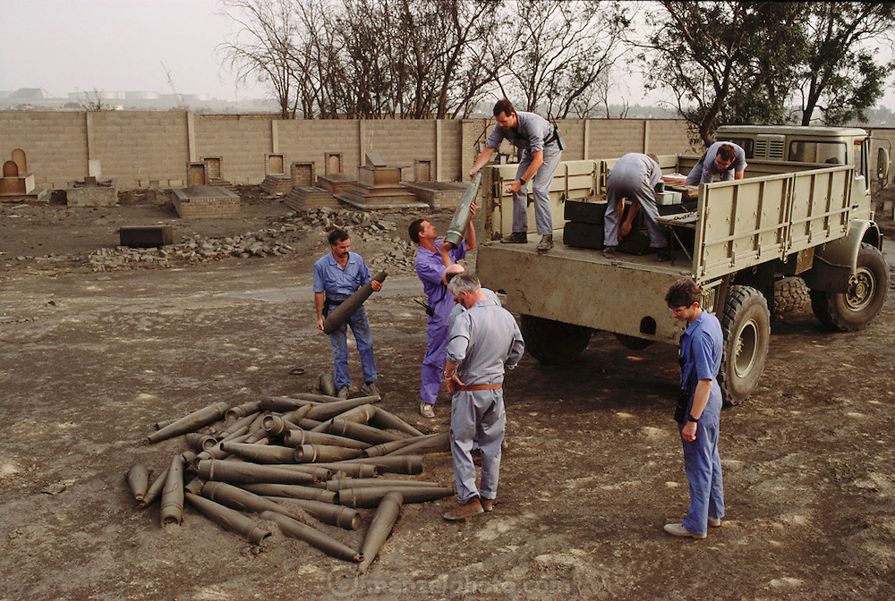 British Explosive Ordinance Disposal Team in an Ahmadi Moslem graveyard loading artillery shells on a truck for disposal. Huge amounts of munitions were abandoned in Kuwait by retreating Iraqi troops in February, 1991. Also, nearly a million land mines were deployed on the beaches and along the Saudi and Iraqi border. In addition, tens of thousands of unexploded bomblets (from cluster bombs dropped by Allied aircraft) littered the desert.