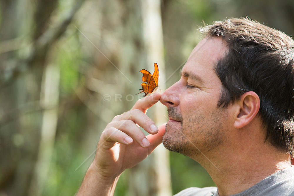 man with a beautiful orange butterfly on his finger outdoors in The Everglades