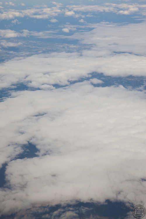 Aerial photograph of some clouds above land from an airplane window.