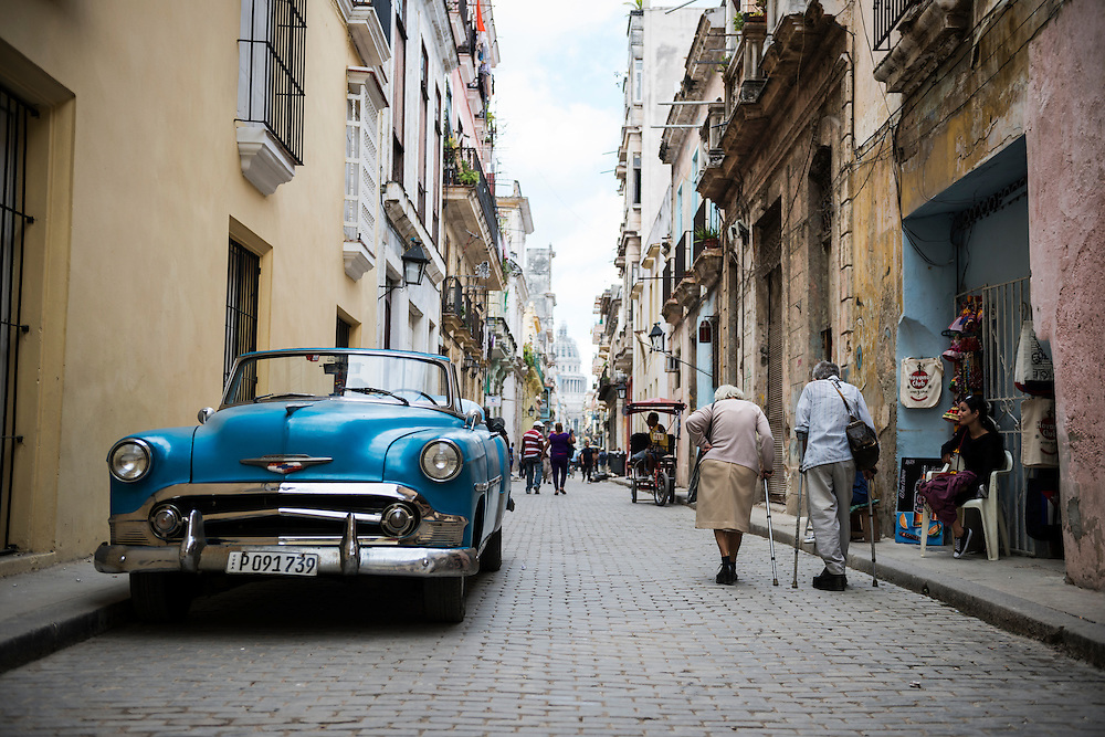Two elderly people walk past an old American car in Havana Vieja, the historic heart of Havana, Cuba (December 2014)