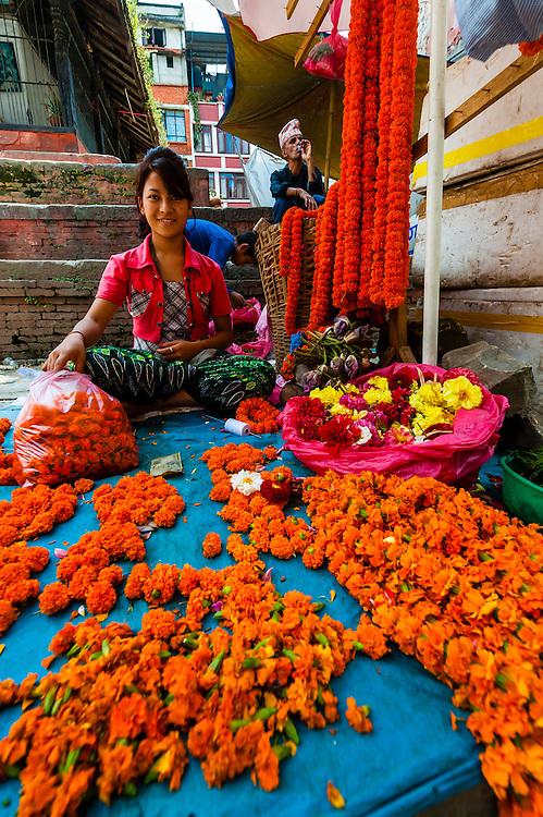 Woman selling garlands of marigolds on the street in Kathmandu, Nepal.