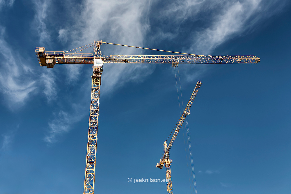 Two cranes against blue sky. Construction work.
