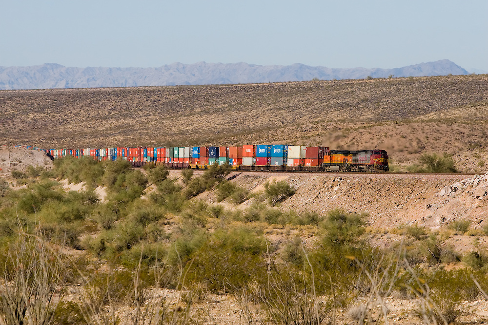 A long BNSF train made of international containers crosses the Arizona desert.